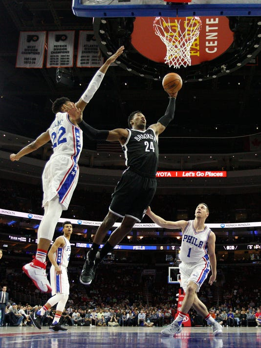 Brooklyn Nets' Rondae Hollis-Jefferson, center, drives between Philadelphia 76ers' Richaun Holmes, left, and T.J. McConnell, right, during the first half of an NBA basketball game, Tuesday, April 4, 2017, in Philadelphia. (AP Photo/Chris Szagola)