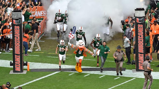 Miami Hurricanes mascot Sebastian and coach coach Manny Diaz run onto the field before a game at Hard Rock Stadium last season.