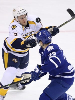 Predators defenseman Anthony Bitetto tries to settle an airborne puck against Maple Leafs right wing Mark Arcobello at Air Canada Centre.