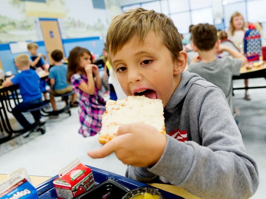 Kindergartner Kurtlyn Hanrahan eats a slice of pizza at Gibbs Elementary School in Corryton, Tennessee on Tuesday, September 5, 2017. Knox County Schools has worked to reduce sodium content and increase whole grains in school lunches as well as offering more vegetables and fruits .