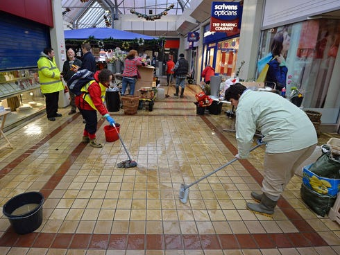 People mop the floor at the Angel Centre retail centre in Tonbridge in south-east England, on December 27, 2013, following recent floods.