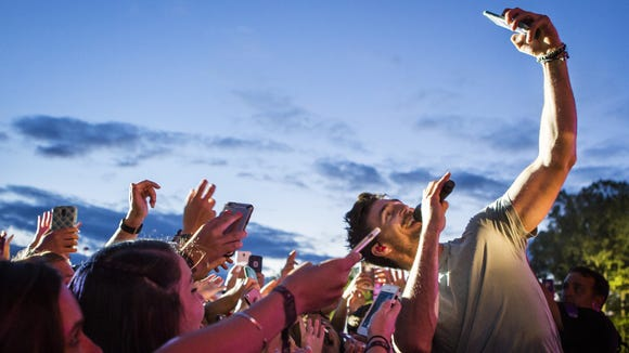 Jake Owen takes a selfie with fans in the crowd as he performs at the Big Barrel Country Music Festival on Sunday.