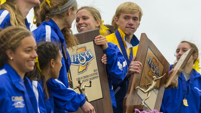 Carmel boys and girls teams celebrate their victories with their trophies following the IHSAA Cross Country State Championship race at LaVern Gibson Championship Cross Country Course in Terre Haute, Ind. Saturday, Oct. 31, 2015. Carmel teams won both the boys and the girls titles.