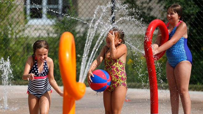 From left, Chelsey Rennert, Malory Goeckerman and Anna Bledsoe play in the new splash pad at North Fond du Lac's pool.