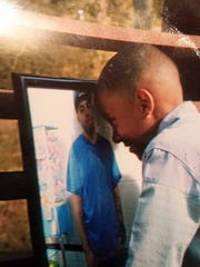 A photo of AJ looking at his slain father's photo floated