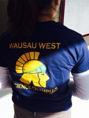 Wausau West High School senior Callie Mataczynski shows her Science Olympiad team's logo on her shirt at a regional competition Saturday at the University of Wisconsin Marathon County in Wausau.