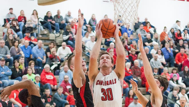 Coldwater's Brady Beckhusen (30) goes up for a layup between Marshall defenders on Jan. 26, 2018.