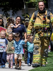 Firefighters and sheriff's deputies escort children