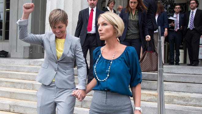 FILE: Melanie and Vanessa Alenier walk out of the Miami court house after the hearing on gay marriage in Miami, Wednesday, July 2, 2014. They are two of the plaintiffs in the case. Attorneys for gay couples and the state of Florida are squaring off at a hearing on a lawsuit challenging Florida's constitutional ban on same-sex marriage.  Like others filed across the country, the lawsuit contends the gay marriage ban added by voters to the state constitution is discriminatory and violates equal protection guarantees.