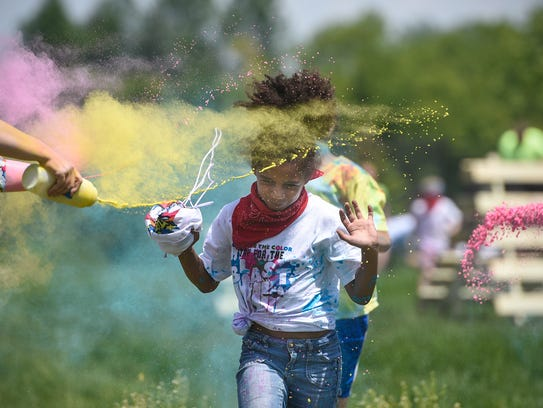 Students run through clouds of colored powder during