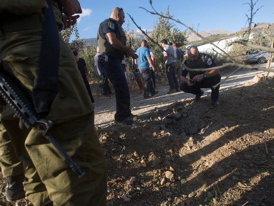 Israeli police and local Druze citizens inspect a plantation hit by a projectile launched from Syria near the Druze village of Majdal Shams, in the Golan Heights, Israel, on Sept. 13, 2016. The Syrian civil war is raging across Israel's northern border.