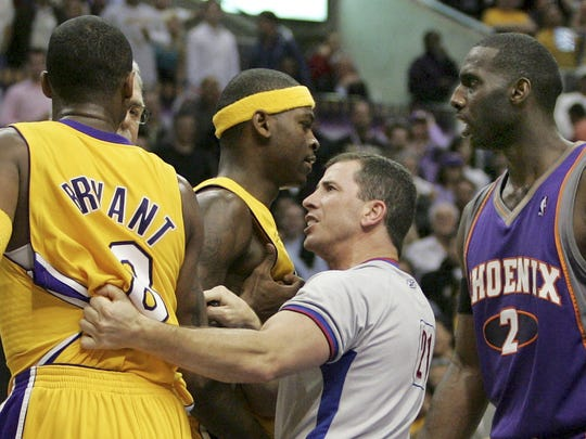 NBA official Tim Donaghy separates Phoenix Suns and Los Angeles Lakers players during a 2006 game.
