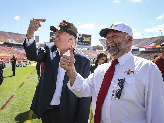Former Iowa State president Steven Leath, right, and President Donald Trump, then a candidate, greet fans on the field prior to the 2015 Iowa-Iowa State football game in Ames, Iowa.