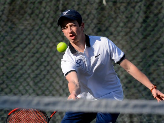 Dallastown's Jonathan Burns returns a serve to Tennison Metz of Dover during the #1 ranked match, Monday, March 19, 2018. Burns defeated Tennison 6-0, 6-0. John A. Pavoncello photo