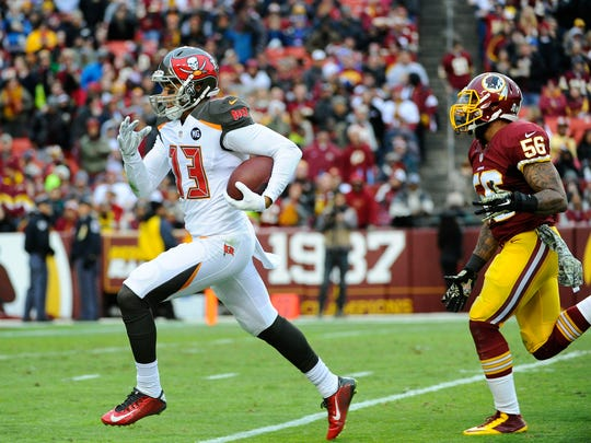 Tampa Bay Buccaneers wide receiver Mike Evans (13) runs with the ball to score a touchdown as Washington Redskins inside linebacker Perry Riley (56) chases during the second half at FedEx Field. The Buccaneers won 27 - 7.