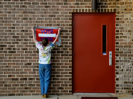 "Jonathan Cunnings, 12 of Dallastown, re-affixes a ""VOTE HERE"" sign outside the polling place at Dallastown Fire Company during last year's election."