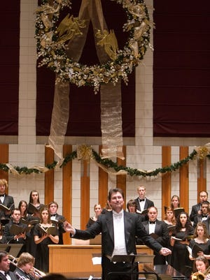 Wallace Long, director of choirs, leads a group during Christmas in Hudson Hall.