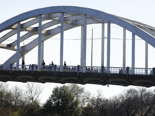Former President Barack Obama and members of congress walk across the Edmund Pettus Bridge during a civil rights commemoration walk in downtown Selma on March 7, 2015.