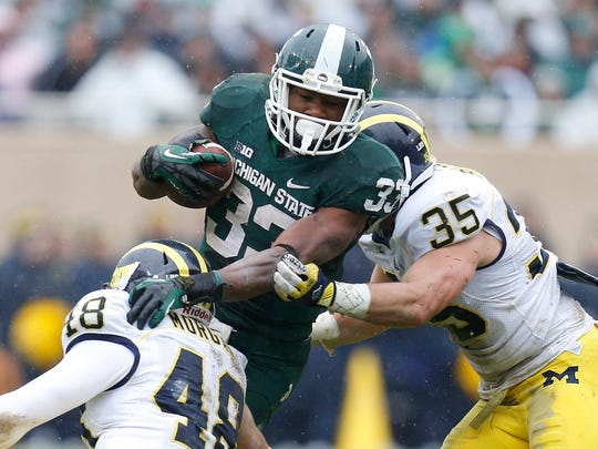 Michigan's Desmond Morgan and Joe Bolden bring down MSU RB Jeremy Langford in the second quarter at Spartan Stadium on Nov. 2, 2013.