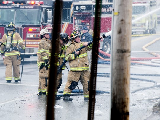 Firefighters work on the scene of a house fire in the