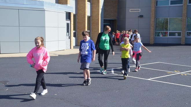 Highland View Principal Tracy Flater joins students on a celebratory walk after the assembly where Highland View celebrated winning the 2017 Active Schools National Award.