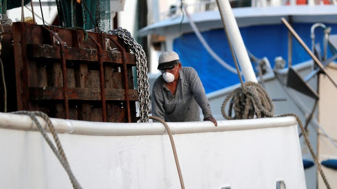 Minh Nguyen, wearing a mask out of fear of the catching the coronavirus, cleans his shrimp boat May 11 in Morgan City. He said he would not be going out for the start of shrimp season due to low prices and fear of the virus.