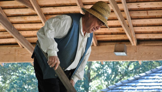 Kent Plantation House volunteer and tour guide Geroge Rogers shows visitors how syrup is made during Sugar Day, held Saturday.