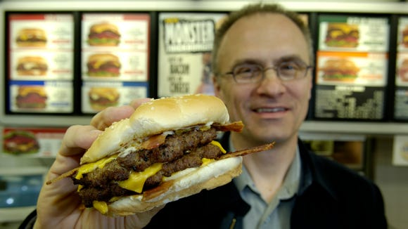 Andy Puzder, President and CEO of CKE Restaurants, shows off one of their Monster Thick Burgers in 2005.