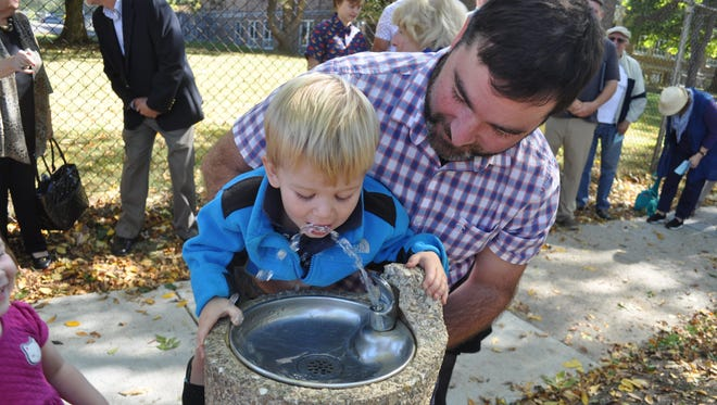 Ryan Thompson holds up his 1-year-old son, Bruce, to drink out of a water fountain recently installed near the corner of Hampton Road and Marlborough Drive in Whitefish Bay. Thompson is a relative of Daniel McCue, who raised money for the drinking fountain before he died in 1989 at the age of 27.