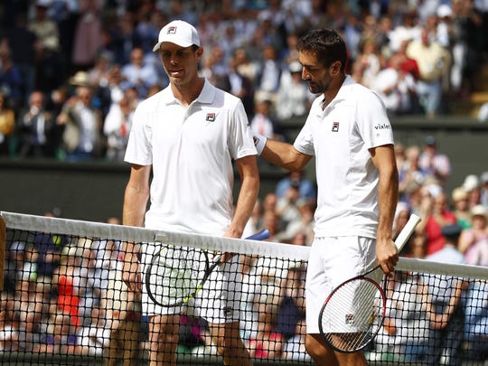 Thousand Oaks High graduate Sam Querrey and Croatia's Marin Cilic greet each other at the net after Querrey's four-set loss in the Wimbledon semifinal Friday.