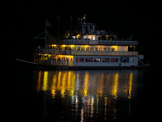Guests ride aboard the Hariott II riverboat on a night