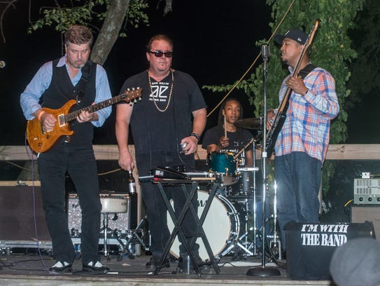 King Bee performs on stage. A fundraiser for John Bull