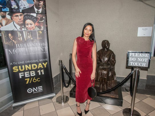 Meta Golding stands next to a statue of Rosa Parks,
