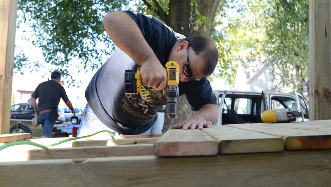 Cliff Reschke, of Memphis, screws down decking on a ramp at a home in Port Huron. The project funded by the United Way brings help to people in the community and provides skills to those who might not have the opportunity to learn them other wise.