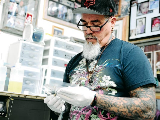 Owner and artist at The Pierced Buddha tattoo and body piercing studio, Greg Knuppel, on Tuesday puts a needle in a machine he uses to tattoo his customers at his store in Aztec.