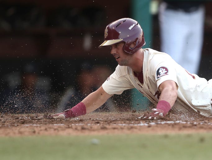 FSU's Reese Albert slides into home plate, scoring