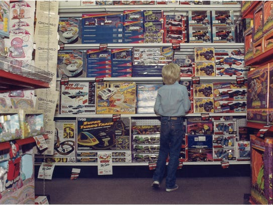Cade Harguess is surrounded by toys during a Sunday afternoon shopping visit to a toy store at Sunset Mall on Nov. 29, 1987.