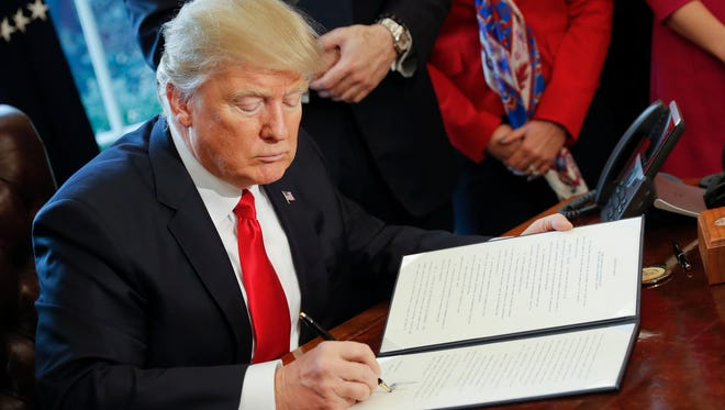 President Trump signs an executive order in the Oval Office on Feb. 3.