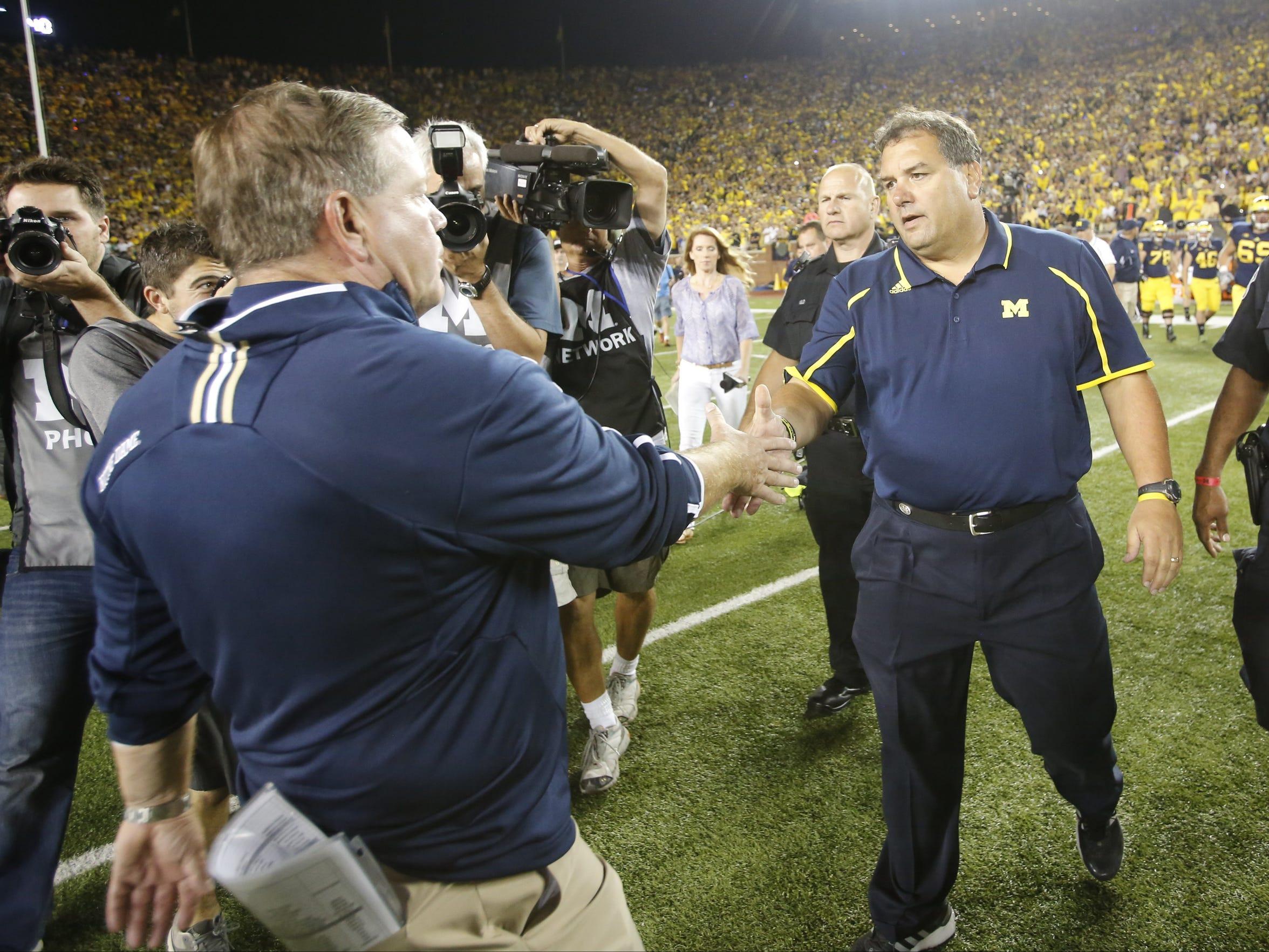 Notre Dame head coach Brian Kelly and Brady Hoke shake