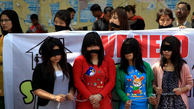 FILE - In this March 8, 2014 file photo, Myanmarese refugee women handcuff, blindfold and cover their mouths with black cloths during a protest on International Women's Day in New Delhi. Myanmarese in Delhi alleged their government used forms of violence against women as weapons of war and demanded an end to it. (AP Photo/Tsering Topgyal, FIle)