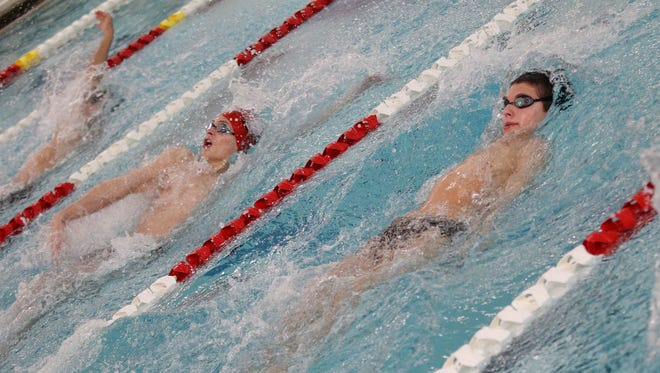 Battling against each other in the 100-yard backstroke Thursday are Canton's Kyle Amick (left) and Plymouth's Keegan Kendall.
