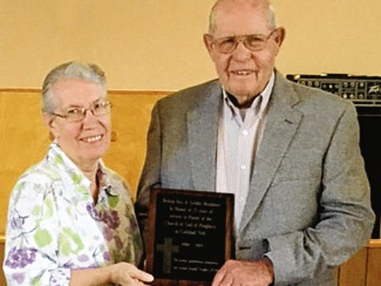 Ray and Goldie Bradshaw pose with a plaque given to Ray Bradshaw for his years of service.