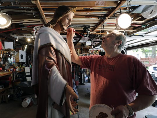 Bruce Nufer, a retired art teacher, paints a near life-size plaster statue of Jesus on Tuesday at his home in Menasha. It will take about 30 hours of work for Nufer to plaster and paint the statue that was located in St. Patrick's School but will be returned to St. Patrick's Parish in Menasha.