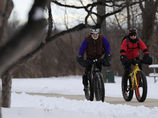 Cyclists ride along the Fox River Trail in Green Bay. Four-season trail access on the Fox River Trail is a community win for well-being.