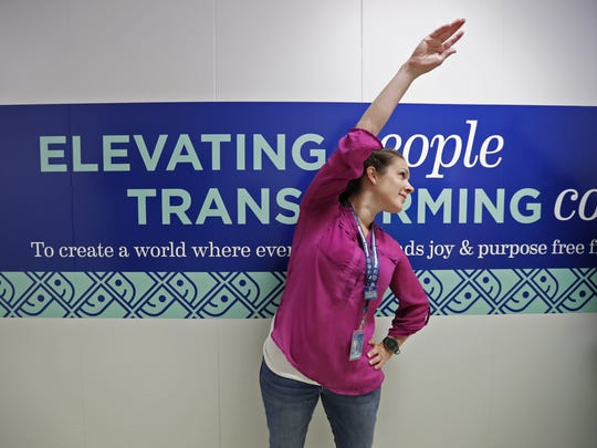 Employee Kendl Behling stretches to start off the day at Goodwill North Central Wisconsin in Menasha, part of the Circles of Care wellness program.