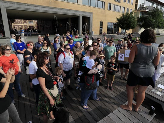 Community members gather at a rally for peace Tuesday on CityDeck in Green Bay. Organizers held the rally as a response to the violence in Charlottesville, Va., over the weekend.