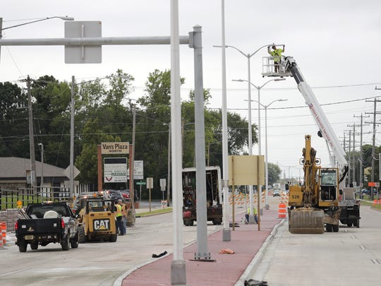 James Lewis, an employee of Bodart Electric Service Inc., installs street lights near the new roundabout at Northland Avenue and Richmond Street in Appleton. The roundabout has been open since Sept. 1.