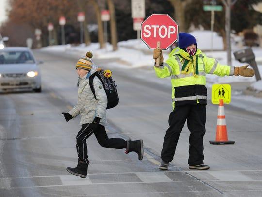Student Henry Poulsen runs to school in frigid temperatures as crossing guard Stella Cross provides safe passage at Edna Ferber Elementary School in Appleton.