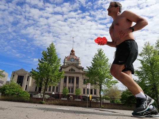 A runner passes the Brown County courthouse in the Cellcom Green Bay Marathon on Sunday, May 20, 2018 in Green Bay, Wis. 