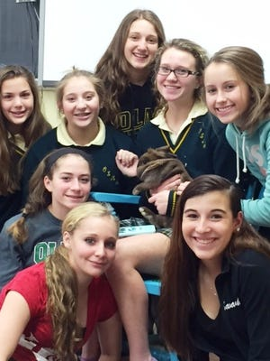 Our Lady of Mercy Academy freshman take time out to visit with Luna, a rabbit the class recently rescued and now cares for at its new home in the academy's biology lab.